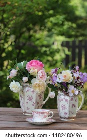 Flowers in antique faience pitcher, fresh coffee in vintage porcelain cup on aged table on fence background, garden scene, floral composition, morning light, vintage style, vertical photo
