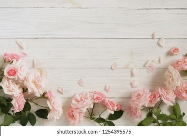 Flowers background. Bouquet of beautiful pink roses on white wooden background.Top view.Copy space