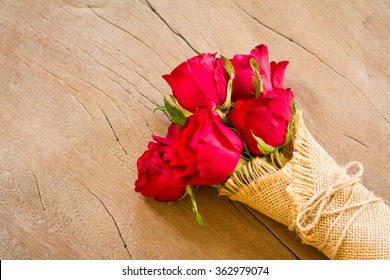 Flowers. Beautiful wedding bouquet of red roses on a wooden background. A gift from the groom on the wedding day. Valentines Day background,
