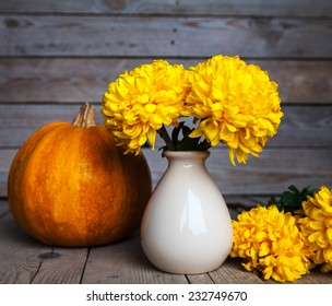 Flowers. Beautiful yellow chrysanthemum in vintage pottery vase. Old wooden background