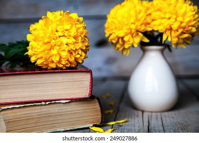 Flowers. Beautiful yellow chrysanthemum in a vintage vase. Cup of coffee. Bright Servais, cup and saucer .. Beautiful breakfast.Old books on a wooden background.