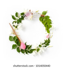 Flowers and beauty accessories composition. Wreath made of bright green leaves, white flowers, perfume, cosmetic brush, bath salt on white background. Spring, summer, beauty blog concept.