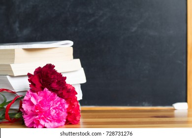 Flowers and blackboard in classroom teacher day background concept