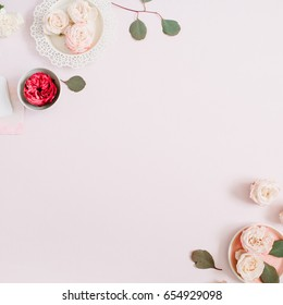 Flowers border frame made of beige and red roses and white carnation on pale pastel pink background. Flat lay, top view. Floral texture background.