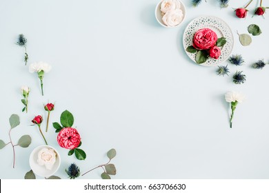 Flowers border frame made of red and beige roses, white carnation and eucalyptus branches on pale pastel blue background. Flat lay, top view. Floral texture background.