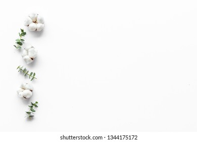 Flowers border with green eucalyptus branches and dry cotton flowers on white background top view copy space