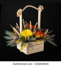Flowers bouquet arrangement in pine basket on black background.  Closeup.