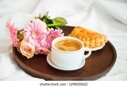 Flowers bouquet with coffee cup and pastry bun on wooden tray in the bed, morning bed breakfast, romantic bed coffee lifestyle