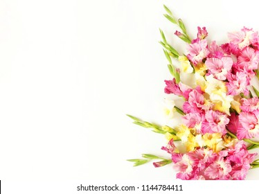 Flowers bouquet of pink and yellow  gladioluses on white background. Pattern of gladioli,  holiday greeting card.  Flat lay, top view. Flowers background. Frame of flowers. Copy space