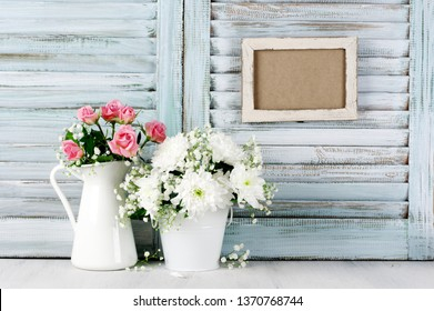 Flowers bouquets on wood table against vintage wooden shutters with empty photoframe. Shabby chic style.