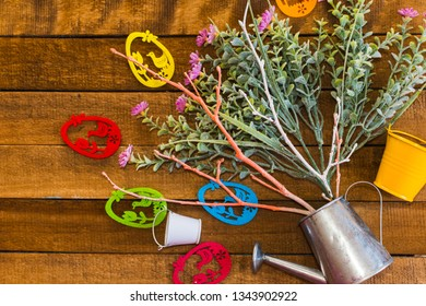flowers and branches in the watering can. colorful eggs laid out on a wooden table. Happy Easter concept