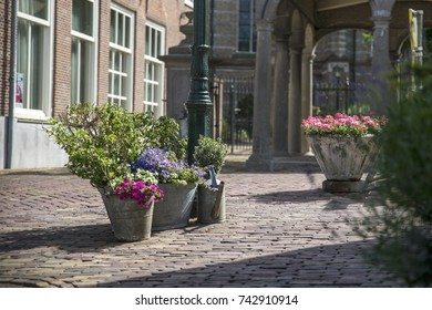Flowers in buckets and a watering can in a street of an historical city in the Netherlands