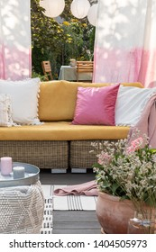 Flowers and candles in front of rattan sofa with colorful pillows on the terrace with drapes. Real photo