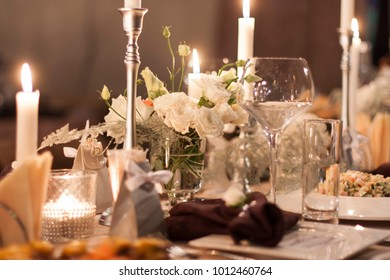 Flowers and candles on laid table on the wedding day