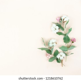 Flowers composition background. Pattern made of pink and cotton flowers and eucalyptus branches on pastel pale beige  background. Flat lay, top view