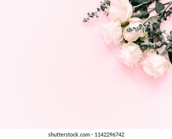 Flowers composition. Border made of white rose flowers and eucalyptus branches on a pink background. Flat lay, top view, copy space