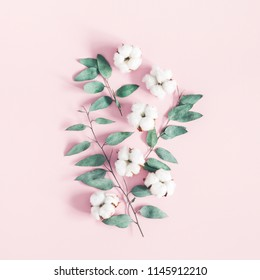 Flowers composition. Eucalyptus leaves and cotton flowers on pastel pink background. Flat lay, top view, square