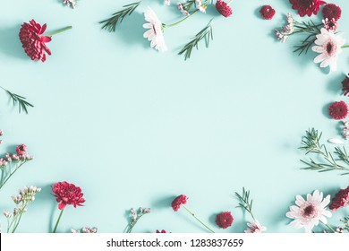 Flowers composition. Eucalyptus leaves and red flowers on pastel blue background. Flat lay, top view