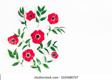Flowers composition. Frame made of anemone flowers and ruscus leaves on white background. Flat lay, top view, copy space
