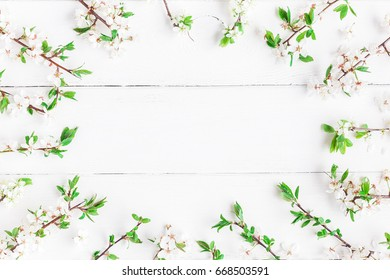 Flowers composition. Frame made of apple tree flowers on white wooden background. Flat lay, top view