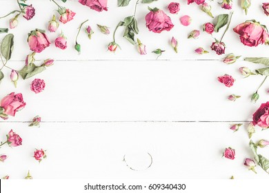 Flowers composition. Frame made of dried rose flowers on white wooden background. Flat lay, top view.