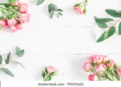 Flowers composition. Frame made of eucalyptus branches and pink rose flowers on white wooden background. Flat lay, top view, copy space.