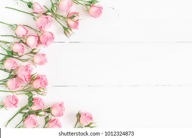 Flowers composition. Frame made of pink rose flowers on white wooden background. Flat lay, top view, copy space.