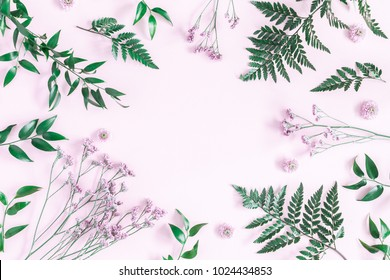 Flowers composition. Frame made of pink flowers and green tropical leaves on pink background. Flat lay, top view, copy space
