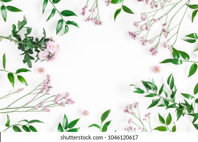 Flowers composition. Frame made of pink flowers and green tropical leaves on white background. Flat lay, top view, copy space