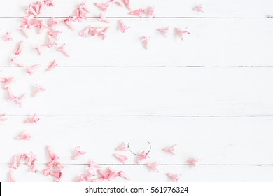 Flowers composition. Frame made of pink flowers on wooden white background. Valentine's Day. Flat lay, top view.
