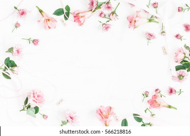 Flowers composition. Frame made of pink flowers and leaves. Top view, flat lay.