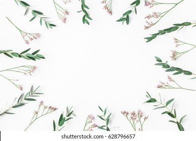 Flowers composition. Frame made of pink flowers and eucalyptus branches on white background. Flat lay, top view