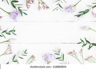 Flowers composition. Frame made of purple flowers and eucalyptus branches on white wooden background. Flat lay, top view