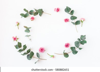 Flowers composition. Frame with rose flowers and eucalyptus branches. Flat lay, top view.