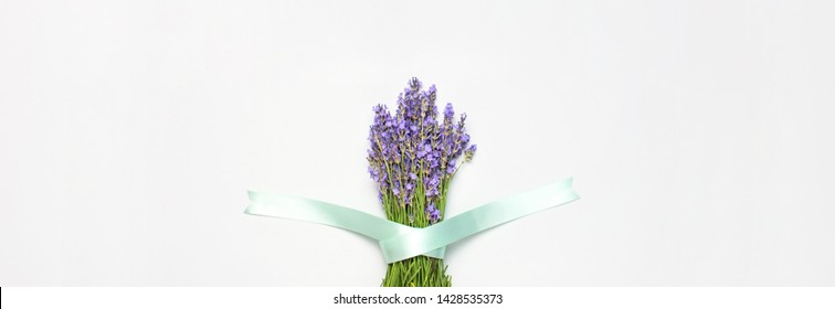 Flowers composition. Fresh bouquet of purple lavender with festive ribbon on light gray background. Flat lay top view copy space. Lavender, floral background, flower card. Minimal concept. Long banner
