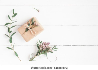 Flowers composition. Gift, pink flowers and eucalyptus branches on white wooden background. Flat lay, top view.