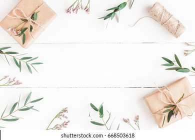Flowers composition. Gifts, pink flowers and eucalyptus branches on wooden white background. Flat lay, top view