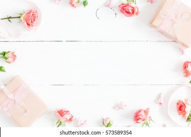 Flowers composition. Gifts and rose flowers on white wooden table. Women Day. Flat lay, top view, copy space