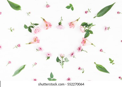 Flowers composition. Heart symbol made of pink flowers and leaves. Top view, flat lay.