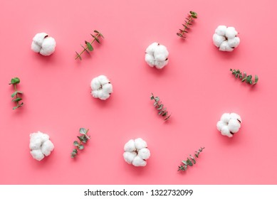 Flowers composition on pink desk with feucalyptus branches and cotton. Flat lay, top view, copy space