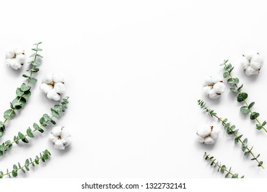 Flowers composition on white desk with fresh eucalyptus branches and cotton. Flat lay, top view, copy space