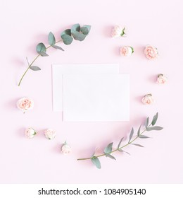 Flowers composition. Paper blank, rose flowers, eucalyptus branches on pastel pink background. Flat lay, top view, copy space