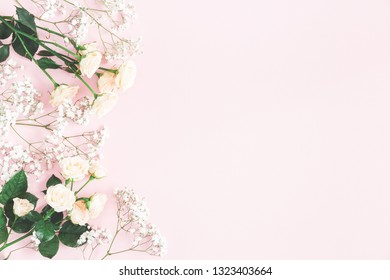 Flowers composition. Rose and gypsophila flowers on pastel pink background. Valentines day, mothers day, womens day concept. Flat lay, top view, copy space