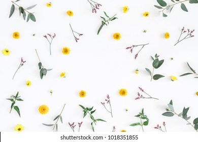 Flowers composition. Round frame made of yellow and pink flowers, eucalyptus branches on white background. Flat lay, top view, copy space.