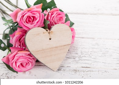 Flowers composition for Valentine's, Mother's or Women's Day. Pink flowers with wooden hearth on old white wooden background. Still-life.