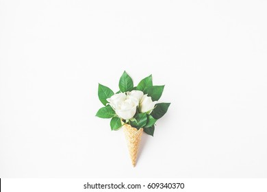 Flowers composition. Waffle cone with rose flowers. Flat lay, top view