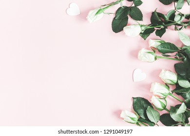 Flowers composition. White rose flowers on pastel pink background. Valentines day, mothers day, womens day concept. Flat lay, top view, copy space