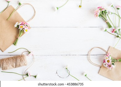Flowers composition. Workspace with small bouquets of daisy flowers, paper packages. Top view, flat lay