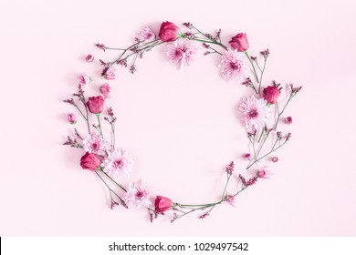 Flowers composition. Wreath made of pink flowers on pink background. Flat lay, top view, copy space