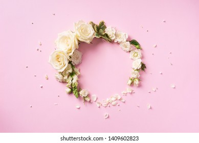 Flowers composition. Wreath made of white roses and rose petals on pink background. Flat lay, top view. Banner with copy space.